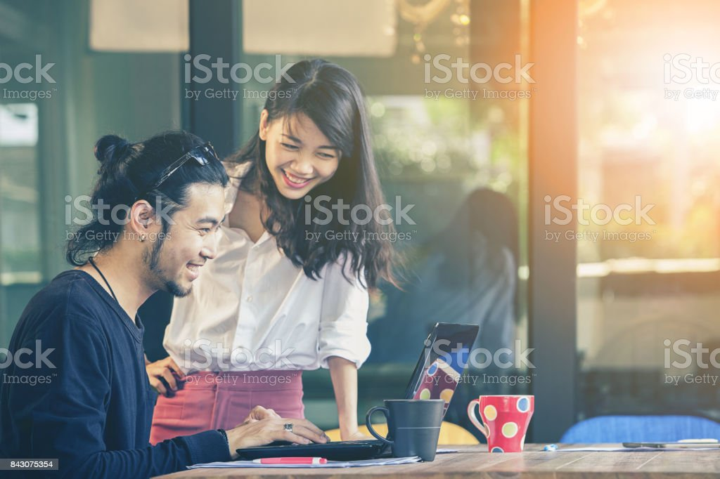 happiness emotion of asian younger man and woman ,freelance team working with computer laptop in home office stock photo