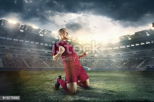 istock Happiness football player after goal on the field of stadium 915275592