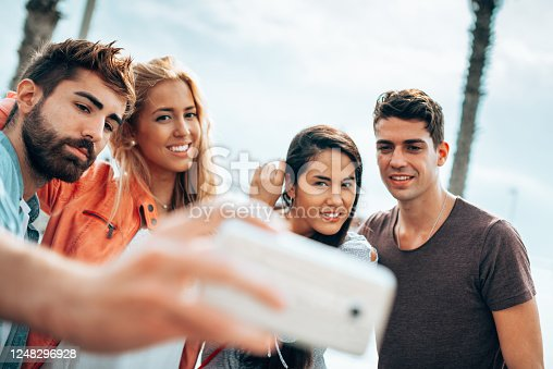 861023492 istock photo happiness friends taking a selfie embracing  outdoors 1248296928