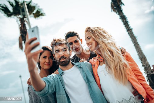 861023492 istock photo happiness friends taking a selfie embracing  outdoors 1248297007