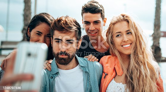 861023492 istock photo happiness friends taking a selfie embracing  outdoors 1248297336