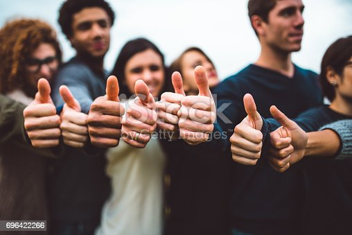 istock happiness friends thumbs up for victory 696422266