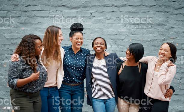 Portrait of a diverse group of young women standing together against a gray wall outside