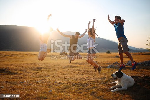 Vintage toned image of a group of friends, enjoying the excursion to the countryside, playing games, jumping, as the sun sets behind the mountains. Taken in Southeastern Europe, at the border of Croatia and Bosnia.