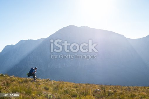 Male hiker walks and admires the amazing view over the mountains above Cape Town, South Africa