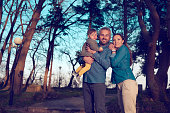 lifestyle shot of young family with baby girl in the park enjoying moments.
