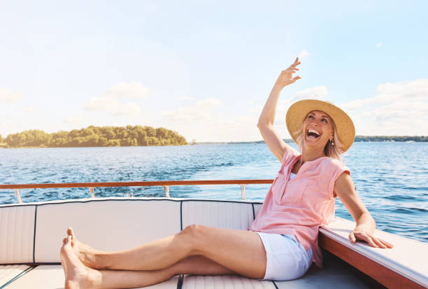 Happiness inspired by a boat ride Shot of a mature woman enjoying a relaxing boat ride only mature women stock pictures, royalty-free photos & images