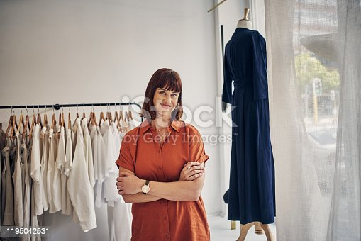 Cropped shot of a young business owner standing with her arms crossed in her clothing store