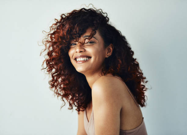 Happiness is the highest level of success Cropped shot of an attractive young woman posing alone against a gray background in the studio curly hair stock pictures, royalty-free photos & images