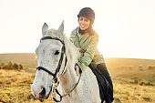 Shot of a young woman riding a horse on a farm
