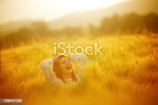 Redhead laughing in nature standing in wheat crop field with eyes closed feeling happy, arms outstretched
