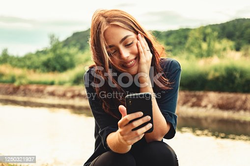 Young happy and lucky smiling woman sitting outdoors by the river looking towards her mobile phone, smiling happy and lucky while having a video call. Real People Outdoor Youth Social Media Lifestyle.