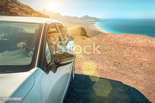 Happiness mother and son, sitting in white car and look on the beautiful ocean coastline view. Freedom, Family, Travel, Journey, Togetherness concept.