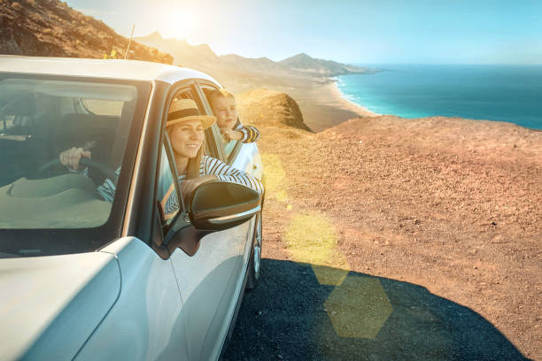 happiness mother and son, sitting in white car and look on the beautiful ocean coastline view. freedom, family, travel, journey, togetherness concept. - road trip стоковые фото и изображения