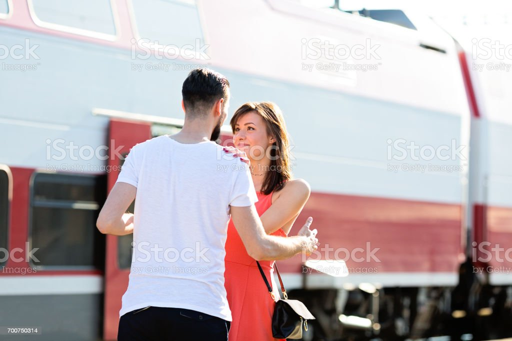 Happiness of a young couple seeing each other again for the first time, warm welcome at the train station during summer sunny day stock photo