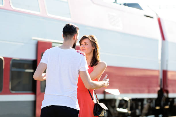 Happiness of a young couple seeing each other again for the first time, warm welcome at the train station during summer sunny day Happiness of a young couple seeing each other again for the first time, warm welcome at the train station during summer sunny day long distance relationship stock pictures, royalty-free photos & images