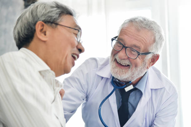 Happiness of Senior male Doctor with Asian male patient. stock photo