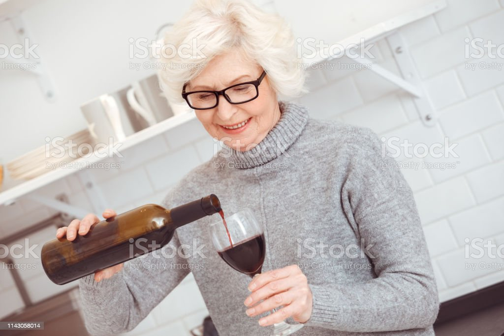Happiness old woman drinks herself. Stage of alcoholism. Indoor,...
