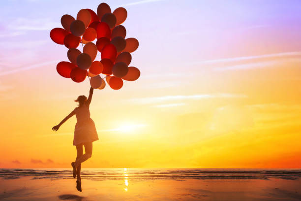 happiness or dream concept, silhouette of happy woman jumping with multicolored balloons - mulher balões imagens e fotografias de stock