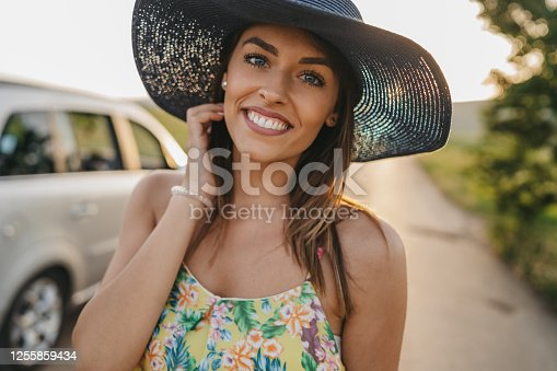 beautiful young woman with blue eyes and blue hat taking break on road trip to enjoy the nature