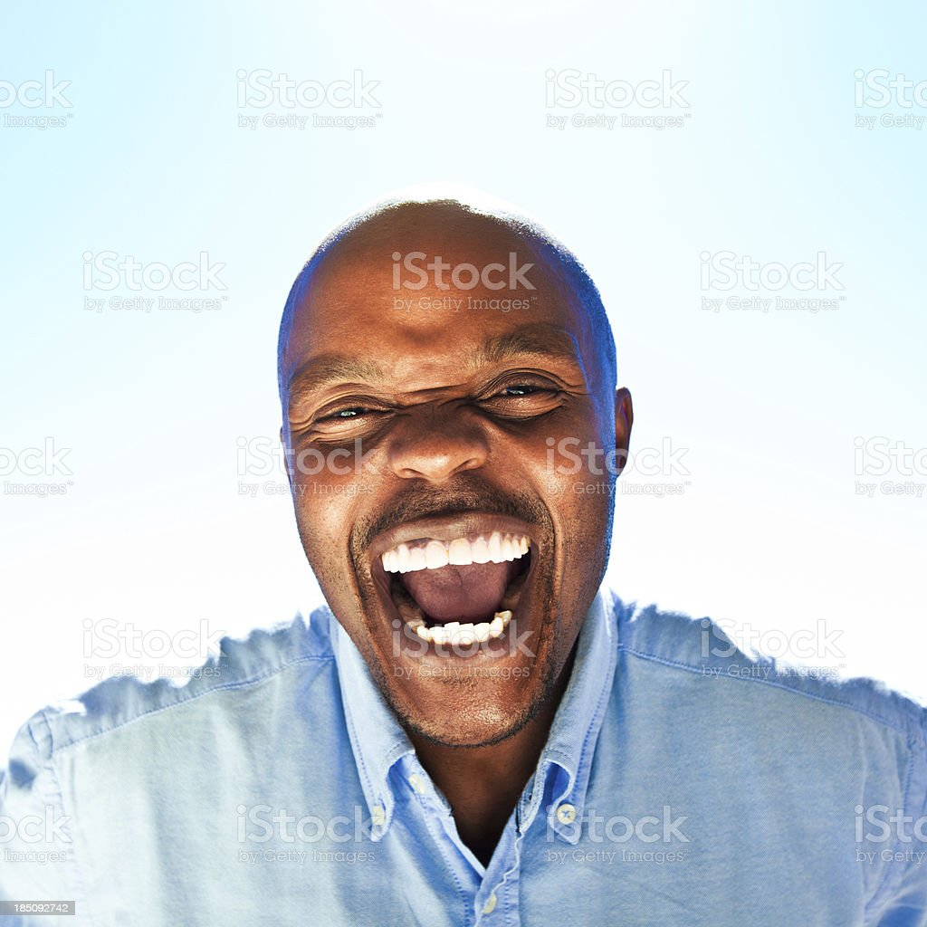 Happiness Happy man laughing at the camera against blue sky. Adult Stock Photo