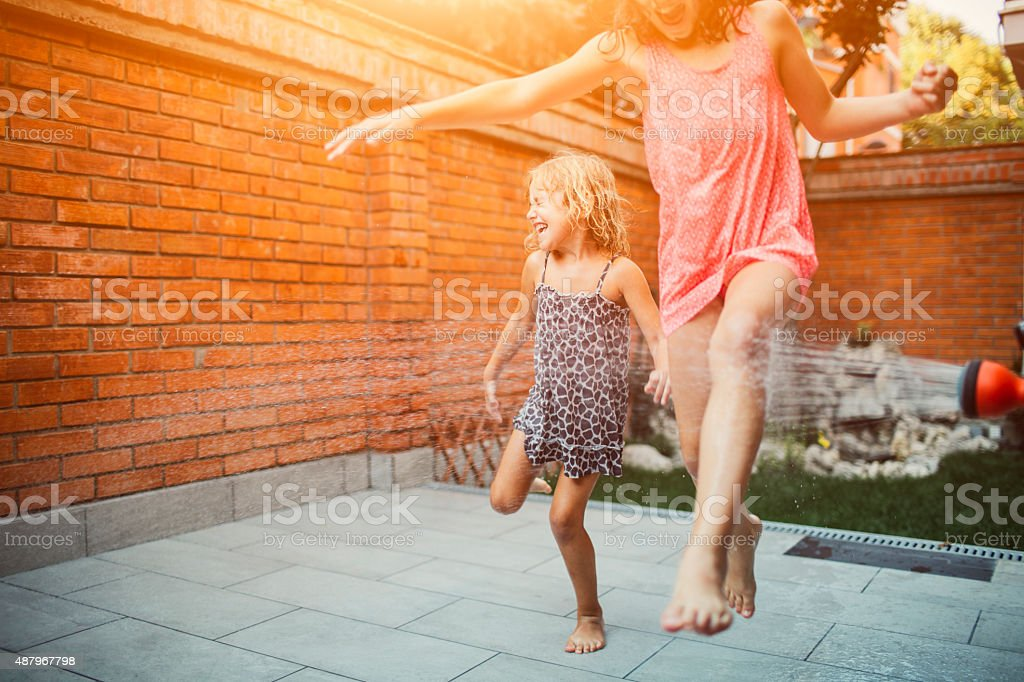Happiness. Two cute girls having fun in their backyard with garden hose. Jumping and running with arms raised. 2015 Stock Photo