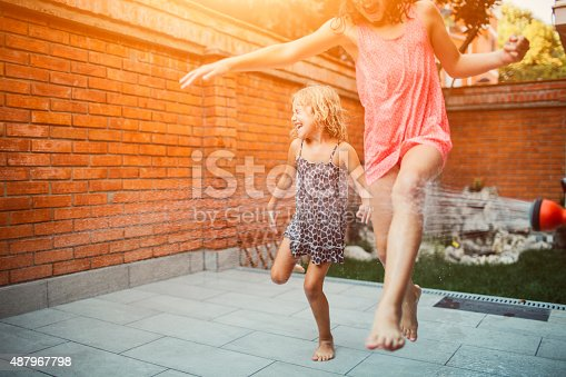 Two cute girls having fun in their backyard with garden hose. Jumping and running with arms raised.
