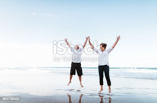 happiness senior couple jumping on the beach