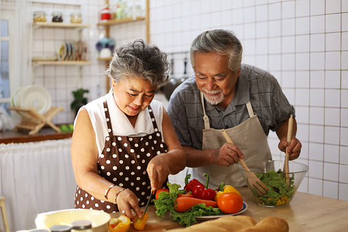 Happiness senior elderly couple having fun in kitchen with healthy food for working from home. COVID-19