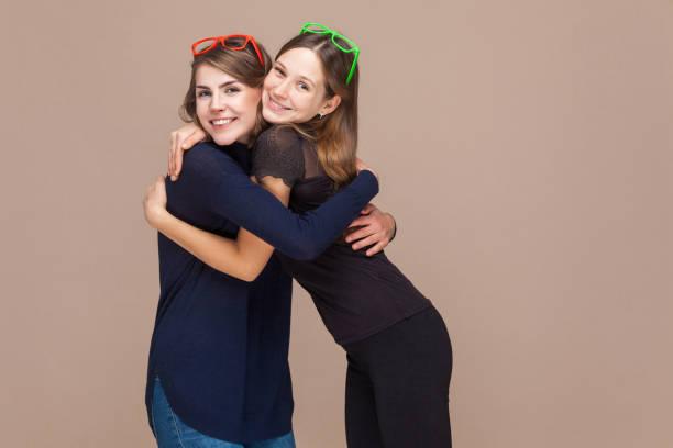 glück schwestern umarmung und toothy lächeln - emoticon hug stock-fotos und bilder
