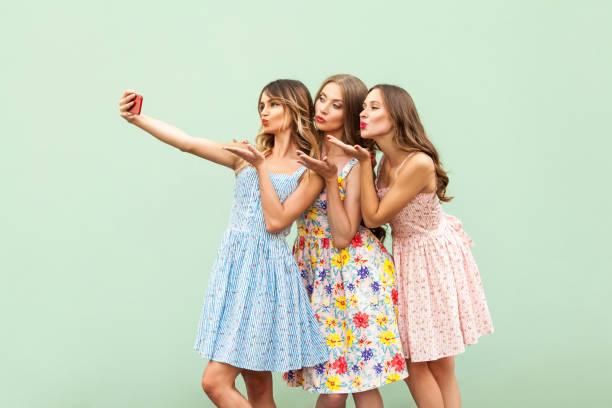 geluk drie jonge volwassen model, macking selfie en verzenden lucht kiss in de slimme telefoon scherm op groene achtergrond. - selfie girl stockfoto's en -beelden