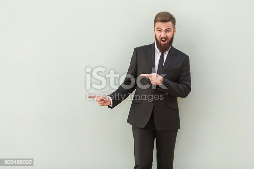 Happiness young man in office wear pointing away while standing against gray background. Studio shot.