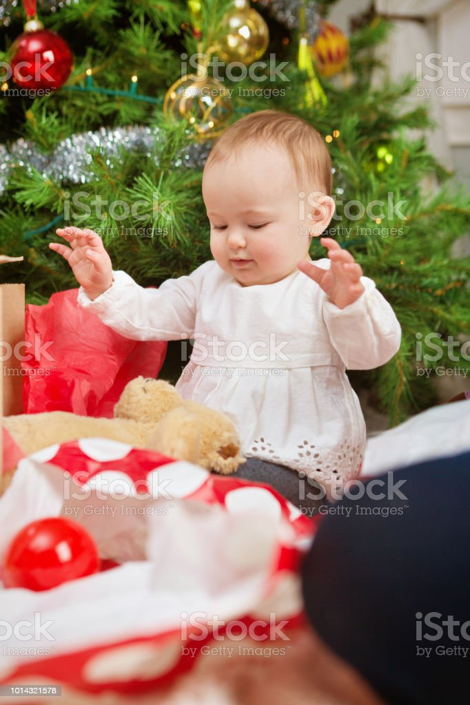 happy 10 months old baby with christmas tree and gift royalty free stock photo