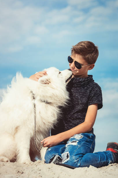 Happy 11 year old boy playing with his dog breed samoyed at the a picture id1068691326?b=1&k=6&m=1068691326&s=612x612&w=0&h=nowdtz1gvyo7 lhtbyu9vetsvminpvwplszedpqf2bm=