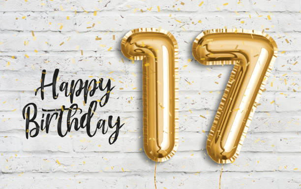 Happy 17th birthday gold foil balloon greeting white wall background. stock photo