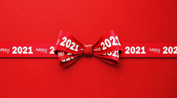 Happy 2021 Written Red Ribbon Sitting over Red Background Happy 2021 written red tied bow ribbon sitting over red background. Horizontal composition with copy space. Happy 2021 concept. cheap stock pictures, royalty-free photos & images