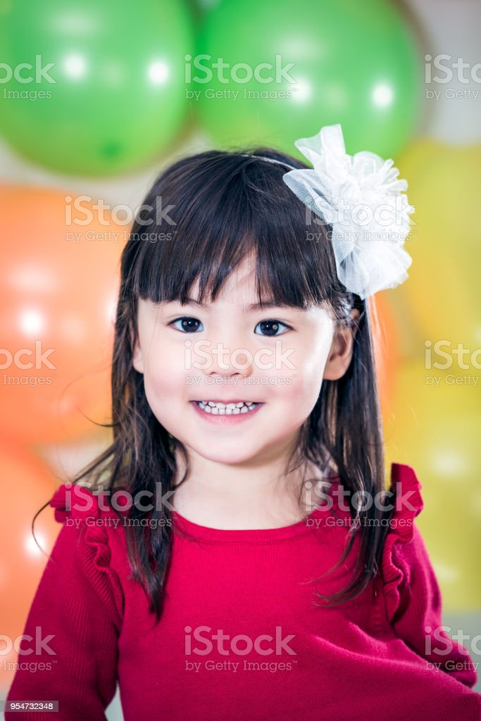 Happy 3 Year Old Girl In Front Of Birthday Balloons