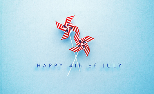 Happy 4th of July message and paper pinwheel pair textured with American flag on blue background. Horizontal composition with copy space. Front view. 4th of July concept.