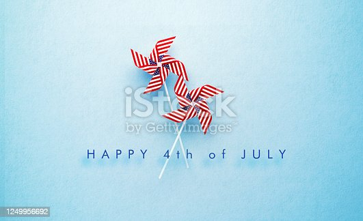 istock Happy 4th of July Message and Paper Pinwheel Pair Textured with American Flag on Blue Background 1249956692