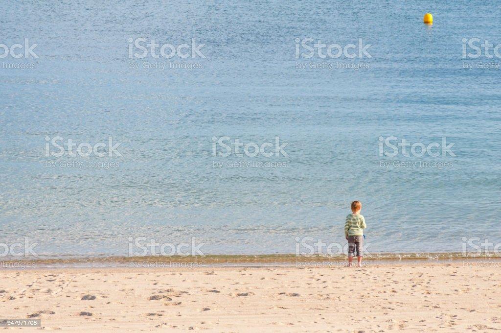 Feliz Nino De 5 Ano De Edad En Pantalones Largos Con Los Pies Descalzos Se Asoma A Pie De Mar En La Playa En Un Dia Soleado Foto De Stock Y Mas