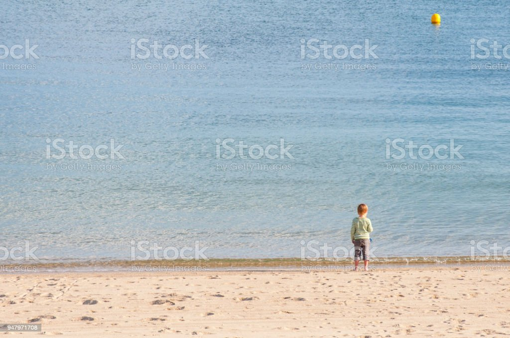 Happy 5 year old boy in long shorts with bare feet looks out to sea standing on sandy beach on a sunny day – zdjęcie