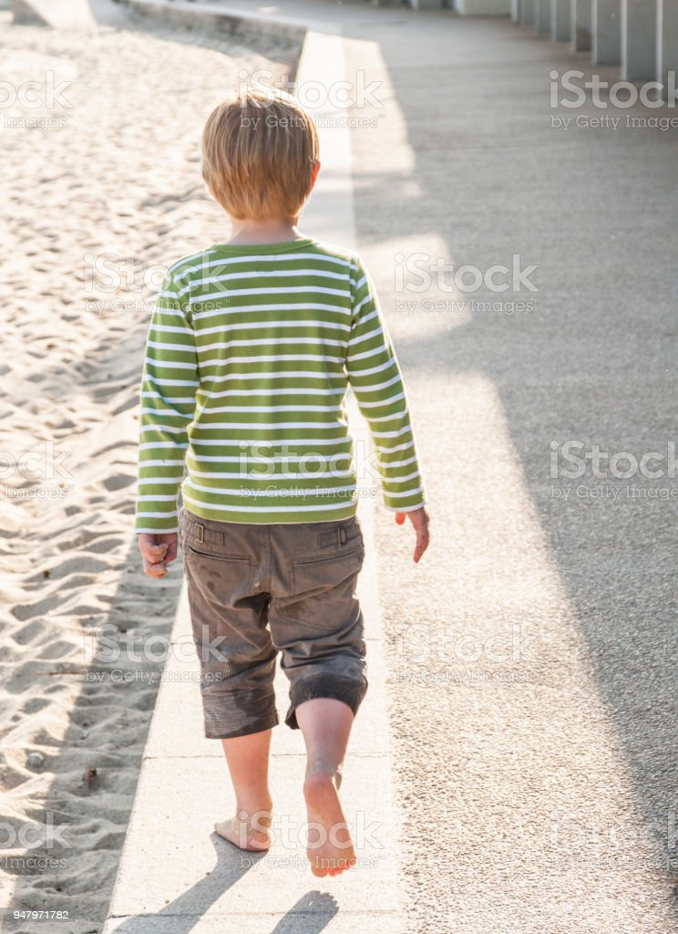 Happy 5 year old boy in long shorts with bare feet walks along concrete wall at the edge of a sandy beach on a sunny day – zdjęcie
