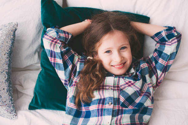 happy 9 years old kid girl relaxing on bed in weekend morning. Smiling preteen girl at home. stock photo