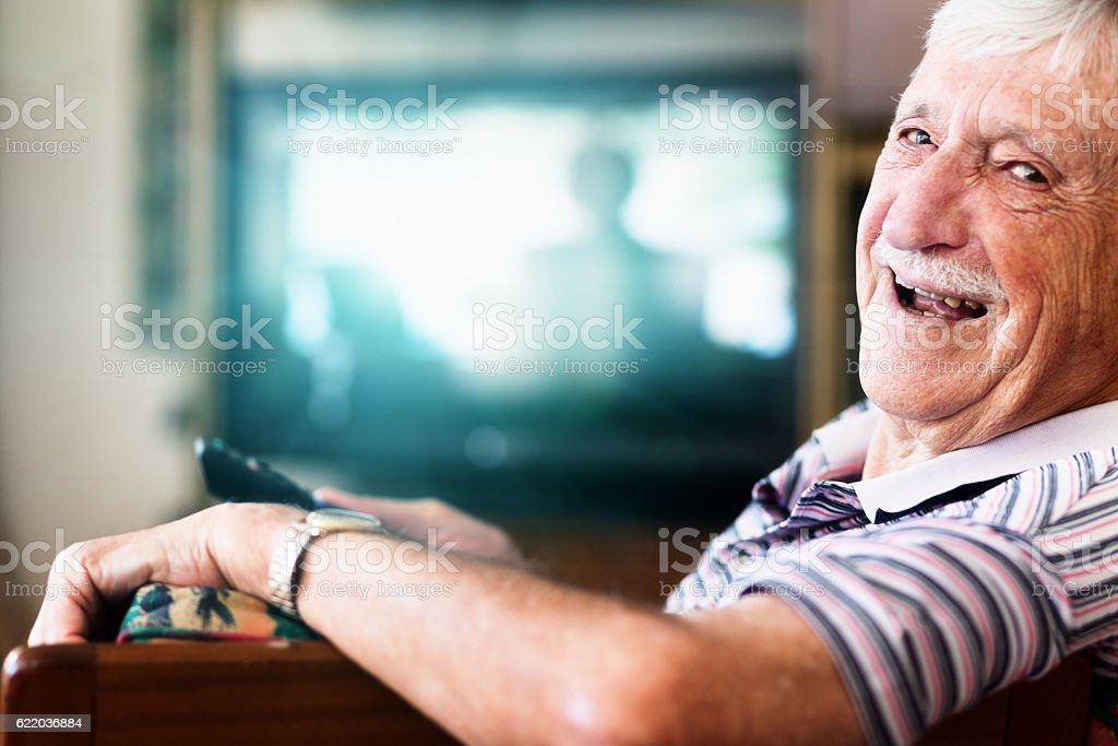 Happy 90-year-old man in charge of the TV remote control stock photo