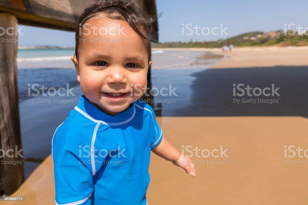Happy Aboriginal Australian Boy Playing at the Beach stock photo