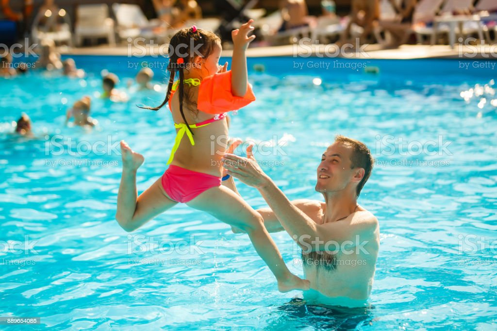 Happy active family young father and his cute daughter adorable toddler girl playing in a swimming pool jumping into the water enjoying summer vacation stock photo