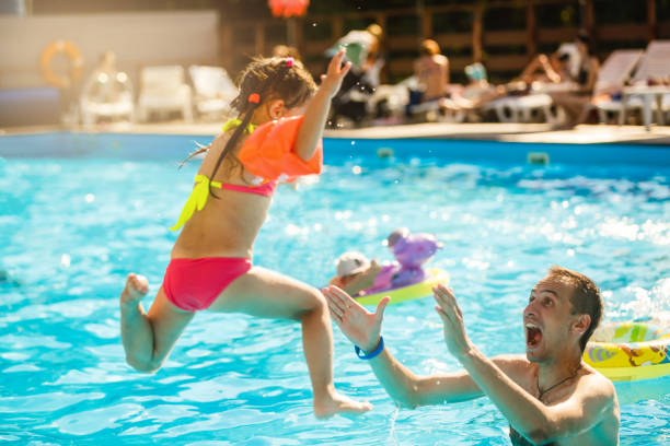 happy active family young father and his cute daughter adorable toddler girl playing in a swimming pool jumping into the water enjoying summer vacation - standing water stock pictures, royalty-free photos & images