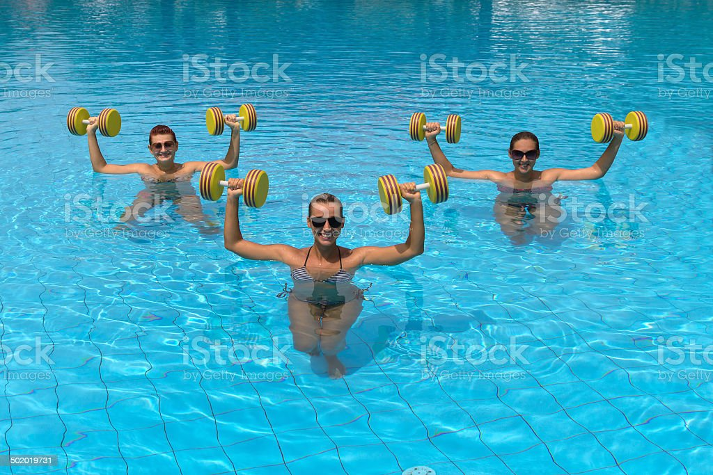 Happy active fitness people doing exercise with aqua dumbbell stock photo