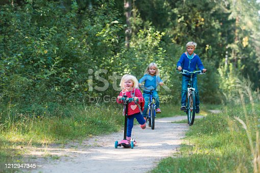 665192886 istock photo happy active kids on bike and scooter ride in nature 1212947345