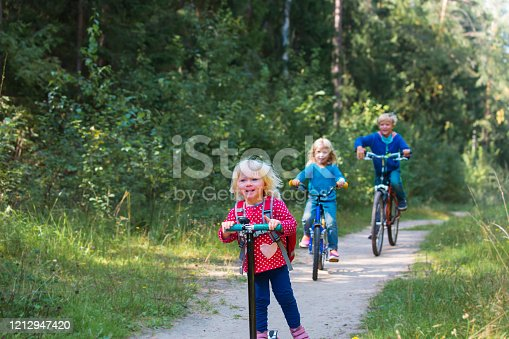 665192886 istock photo happy active kids on bike and scooter ride in nature 1212947420
